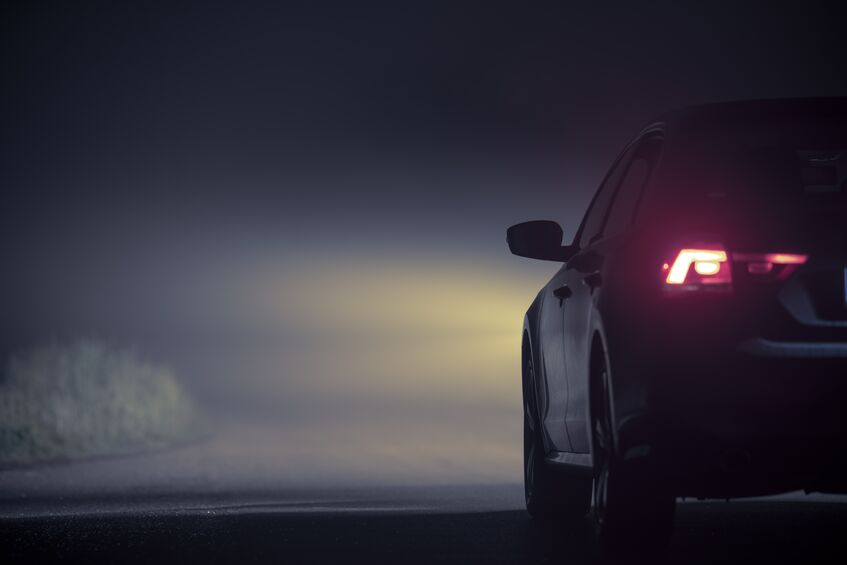 Car driving in fog at night